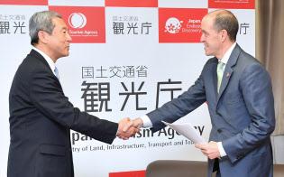 民泊はある種の社会実験だ(田村観光庁長官(左)と握手する米エアビーアンドビーのクリストファー・レヘイン・グローバル政策担当最高責任者。3月、観光庁)