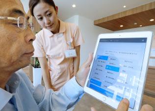 診察を前に待合室でタブレット端末を使って問診に答える通院者(福岡市東区)=一部画像処理しています