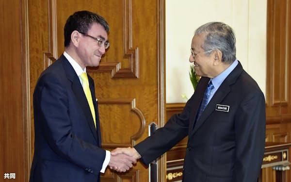 11日、マレーシアのマハティール首相(右)と会談前に握手する河野外相=共同