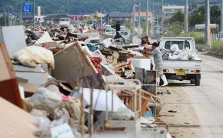 道路脇に積み上げられた家財道具などの災害ごみ(7月12日、岡山県倉敷市真備町地区)