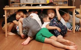 避難訓練で机の下に入って頭を守る「中崎町かいせい保育園」の園児(大阪市北区)