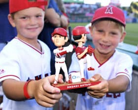 エンゼルス・大谷の「二刀流」首振り人形を手にする子どもたち(12日、アナハイム)=共同