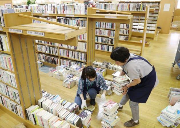 本棚の中仕切りが壊れ、散乱した本を整理する職員ら(大阪府高槻市の阿武山図書館)