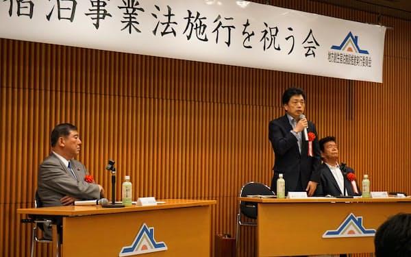 「住宅宿泊事業法施行を祝う会」で説明する観光庁の水嶋次長(中)