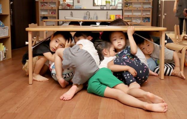 避難訓練で机の下に入って頭を守る「中崎町かいせい保育園の園児(大阪市北区)