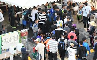 被災地でのボランティア活動のため受付に並ぶ人たち(14日午前、広島市安佐北区)