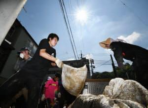 強い日差しの下、土砂で作った土のうを運ぶボランティア(14日午前、広島市安佐北区)