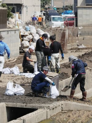 道に残る土砂で土のうを作るボランティア(14日午前、岡山県倉敷市真備町地区)