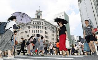 厳しい暑さの東京・銀座で日傘を差して歩く女性(14日午前)=共同