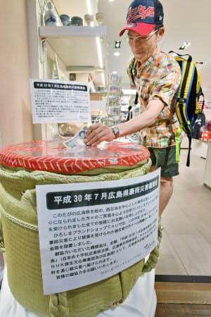 広島県のアンテナショップに設けられた豪雨被災地を支援する募金箱(14日午前、東京都中央区)