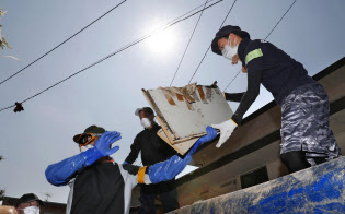 強い日差しの下、片付けを手伝うボランティアら(15日午前9時13分、岡山県倉敷市真備町地区)=共同