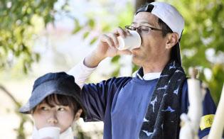 作業の合間、水分を補給するボランティアの男性ら(15日、広島県熊野町)=共同