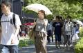 強い日差しの中、日傘を差して歩く女性(15日午後、名古屋市)=共同