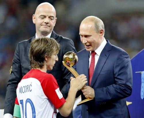 最優秀選手の「ゴールデンボール賞」を受賞したクロアチアのモドリッチ(左)にトロフィーを手渡すロシアのプーチン大統領(15日、モスクワ)=共同