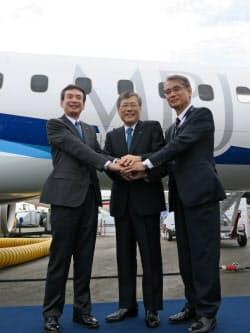 飛行展示終了後、機体の前で握手する(左から)全日空の伊東常務執行役員、三菱重工の宮永社長CEO、三菱航空機の水谷社長(16日、英ファンボロー)