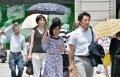 強い日差しの中を歩く人たち(17日午前、東京都中央区)