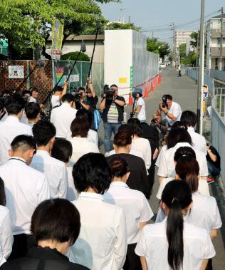 ブロック塀が倒れて児童が亡くなった市立寿栄小の前で黙とうする教職員(18日午前、大阪府高槻市)