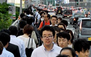 公共交通機関の運転見合わせなどで、徒歩で帰路につく人ら(6月18日、大阪市淀川区の新淀川大橋)