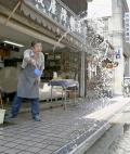 午前中から37度を超える猛暑となった岐阜市内で、店舗の前に打ち水をする男性(18日午前)=共同