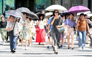 猛暑日の強い日差しの下、日傘をさして歩く人たち(18日午後、東京都中央区)