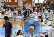 小学校の体育館で避難生活を送る人たち(9日、岡山県倉敷市真備町地区)