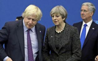 5月、英国のメイ首相(中央)と話すジョンソン氏(左)=AP