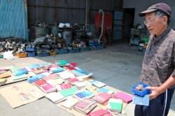 洪水でふやけた商品カタログや書類を日にさらす中山龍太郎さん。奥には廃棄となった自動車部品が並ぶ(19日午後、愛媛県大洲市)