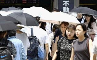 厳しい暑さの中、日傘を差して歩く女性ら(19日午後、東京・JR新宿駅前)=共同