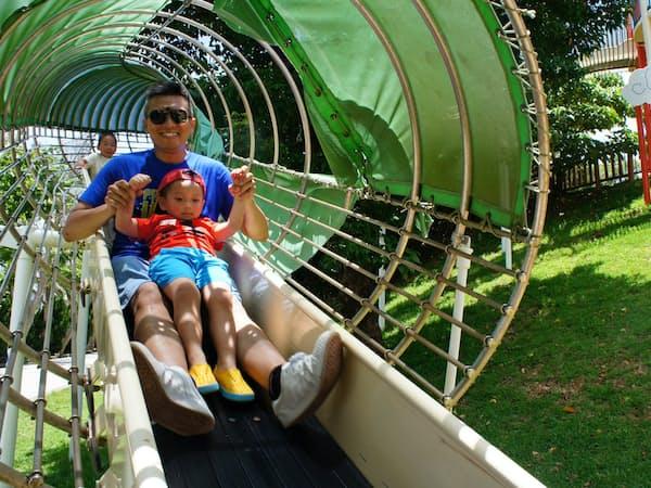 那覇市の奥武山公園の遊具で遊ぶ台湾からの観光客(6月)