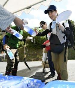 熱中症予防のための飲み物を受け取り、現場へ向かうボランティア(21日午前、岡山県倉敷市)=共同