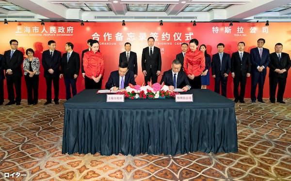 7月10日、上海で開かれた米テスラ工場建設プロジェクトの署名式に出席したイーロン・マスクCEO(後列中央右)と上海市幹部=ロイター
