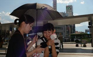 日傘と携帯用の扇風機で暑さをしのぐ親子連れ(23日午後、甲府市)