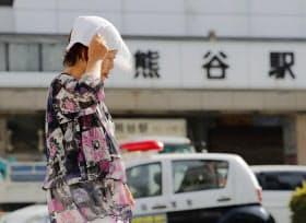 国内最高気温を記録した埼玉県熊谷市で、タオルを頭にのせて歩く女性(23日午後)=共同