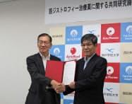 共同研究締結書を手にするアスタファーマシューティカルズの西田社長(左)と神戸学院大の松尾特命教授(富山県上市町)