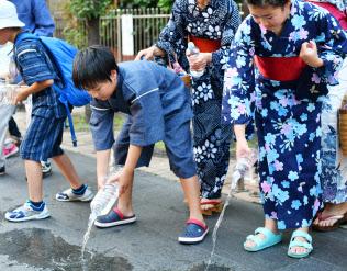 イベントで道路に打ち水をする浴衣姿の人たち(23日午後、東京・港)