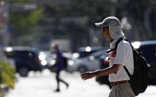 40度に迫る猛暑となった名古屋市の繁華街で道路を横断する男性=23日午後