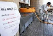 岡山県倉敷市真備町地区全域で水道水が飲めるようになり、給水所を撤去する同市水道局の職員(24日午前)=共同