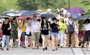 厳しい暑さの中、日傘を差して歩く外国人観光客ら(24日午前、東京都千代田区)=共同