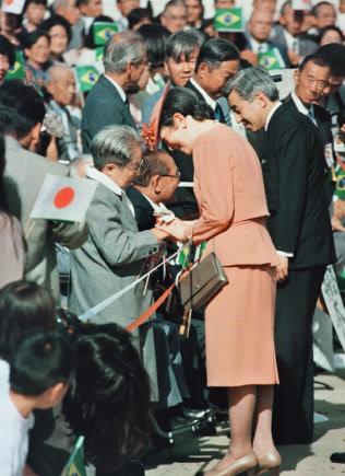 日系人主催の歓迎行事で皇后さまの手を握り涙ぐむ老婦人(1997年、ブラジル・ブラジリアの日本大使館)=時事