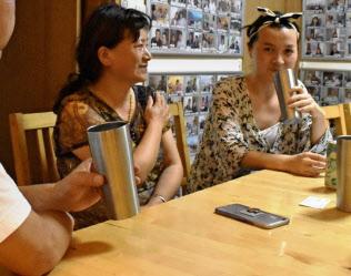 新法での届け出を済ませた民泊の家主(左手前)と談笑する中国人親子(東京都内)