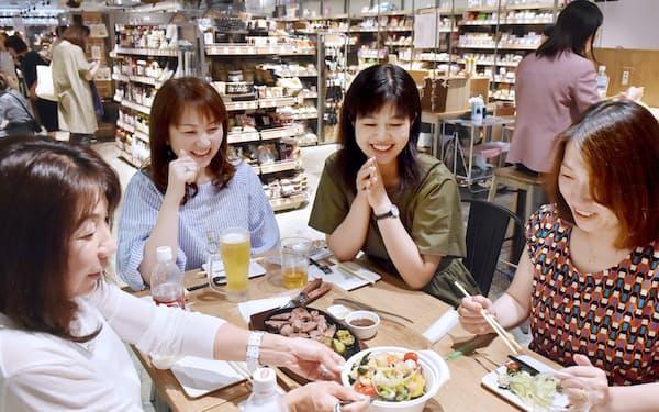 店内で購入した商品を食べる女性客ら(大阪市北区の「キッチン&マーケット ルクア大阪店」)