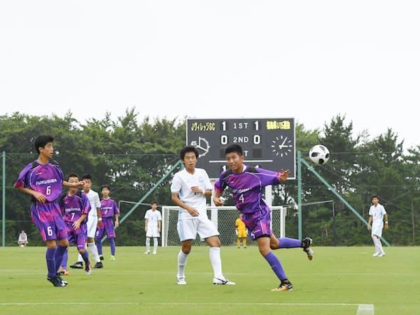 再び時を刻み始めた電光掲示板を前にプレーする地元のサッカー選手(28日午後、福島県広野町)