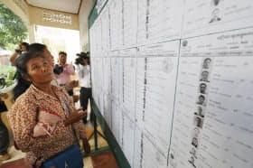 投票所を訪れて投票者のリストが書かれた名簿をみる有権者(29日午前、カンダル州)=小高顕撮影