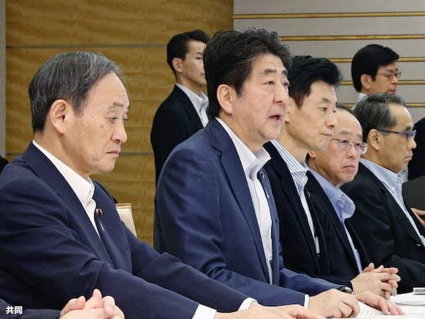 対策本部会議で発言する安倍首相。左は菅官房長官(29日午後、首相官邸)=共同