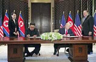 米朝首脳会談後、共同声明に署名する北朝鮮の金正恩委員長(左)とトランプ米大統領(6月12日、シンガポール)=ロイター
