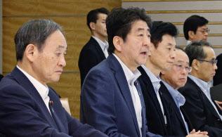 西日本豪雨の対策本部会議で発言する安倍首相。左は菅官房長官(7月29日午後、首相官邸)=共同