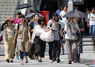 猛暑が続く名古屋市内で、横断歩道を渡る歩行者(3日午前)=共同