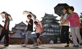 日傘を差して名古屋城を観光する人たち(3日、名古屋市中区)