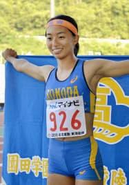 女子走り幅跳びで優勝し笑顔を見せる園田学園・高良彩花(4日、三重交通Gスポーツの杜伊勢)=共同