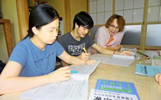 保護施設を運営する岡部文吾さん(右)と日本語を学ぶベトナム人技能実習生ら(6月26日、福島県郡山市)